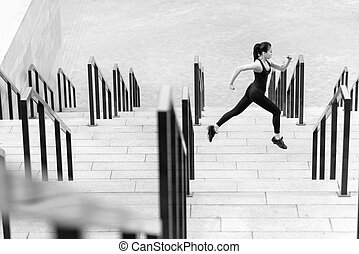 Side view of athletic young woman in sportswear running on stadium stairs, black and white photo