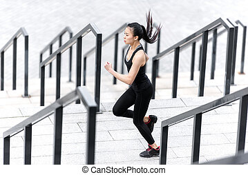 Side view of athletic young woman in sportswear running on stadium stairs