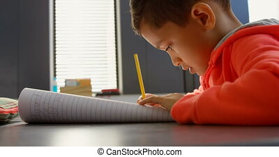 Side view of attentive Asian schoolboy studying at desk in classroom at school. He is writing on notebook 4k