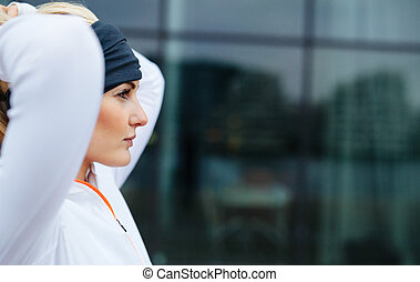 Side view of attractive female athlete ready of a run in city. Confident and motivated fitness woman looking away.
