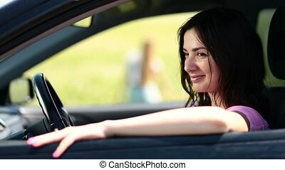 Side view of attractive woman driver in car window