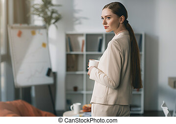 Side view of attractive young businesswoman holding cup and looking away in office