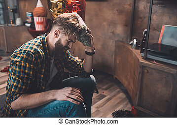 Side view of bearded young man suffering from headache after party