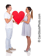 couple holding paper heart symbol