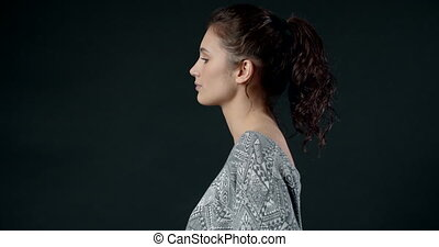 Side view of beautiful young girl with brown curly hair tied in knot wearing casual sweater posing in studio with dark background. Concept of natural beauty and female charisma
