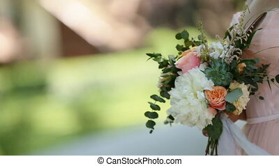 Side view of beautiful smiling young blond woman in the park with bouquet on a warm summer day