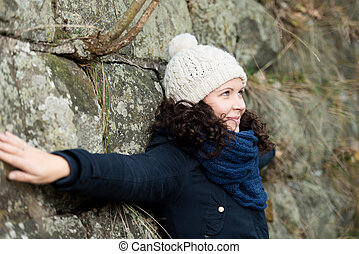 Side view of beautiful young woman in winter clothes with...
