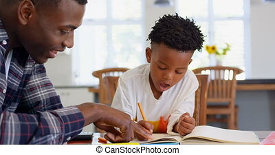 Side view of black father helping his son with homework at comfortable home 4k