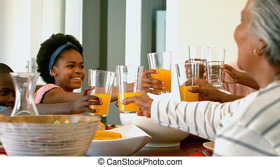 Side view of black multi generation family toasting glass of juice and water at dining table 4k