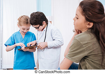side view of bored girl patient with boy doctor and girl nurse using digital tablet behind