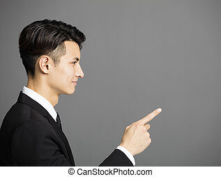 side view of business man pointing at copy space
