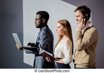 Business people together in meeting room with phone, notepad and laptop