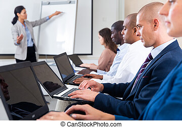 Side view of businessman with laptop participating in business training