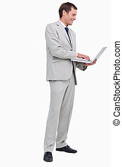 Side view of businessman working on his laptop