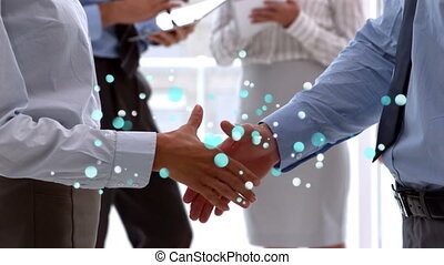 Side view of businessmen shaking hands with sparkling blue light bubbles in foreground