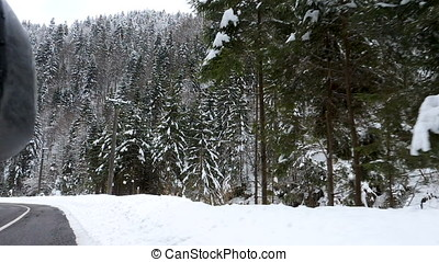 Side view of car driving through mountains in winter