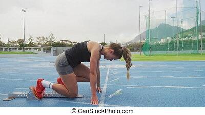 Side view of caucasian athlete preparing for race in stadium...