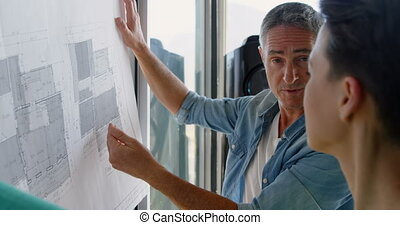 Side view of Caucasian Business people discussing over blueprint in the office 4k