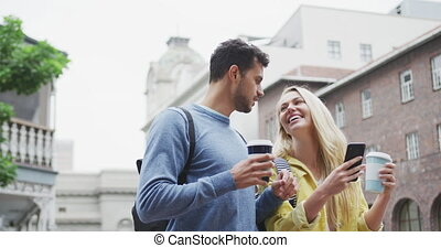 Side view of Caucasian couple on the go holding a takeaway coffee