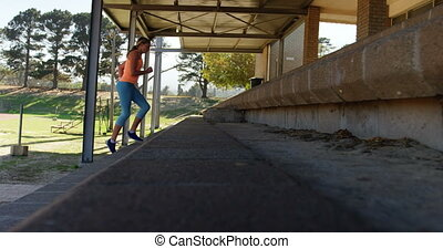 Side view of Caucasian female athlete exercising on steps at sports venue. She is fit and healthy 4k