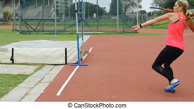 Side view of Caucasian female athlete practicing javelin throw at sports venue. She is fit and healthy 4k