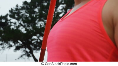 Side view of Caucasian female athlete practicing javelin throw at sports venue. She is focused 4k