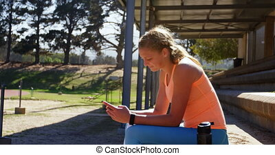 Side view of Caucasian female athlete using mobile phone at sports venue. She is sitting at sports venue 4k