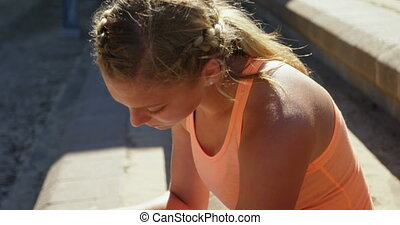 Side view of Caucasian female athlete using smartwatch at sports venue. She is sitting at sports venue 4k