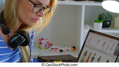 Side view of Caucasian female fashion designer using graphic tablet at desk in office 4k