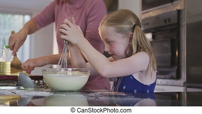 Side view of Caucasian girl cooking with her mother at home...