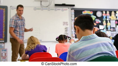 Side view of Caucasian male teacher teaching schoolkids on ...