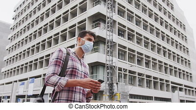 Side view of Caucasian man on the go wearing a corovirus ...
