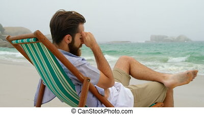 Side view of Caucasian man relaxing on sun lounger at beach ...