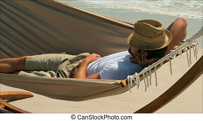 Side view of Caucasian man sleeping in a hammock on the ...