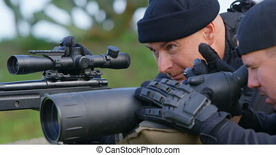 Side view of caucasian military soldiers looking through binoculars and riflescope at training. They are lying on ground and talking with each other 4k