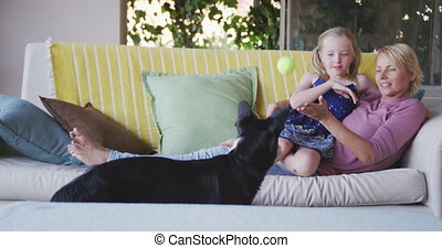 Side view of Caucasian woman and her daughter playing with the dog at home