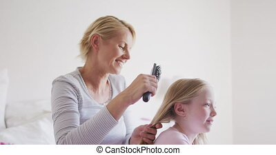 Side view of Caucasian woman brushing hair of her daughter...