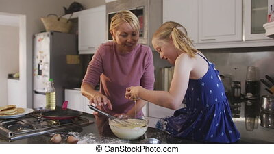 Side view of Caucasian woman cooking with her daughter at ...