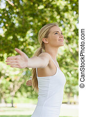 Side view of cheerful attractive woman doing yoga spreading...