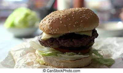 Side view of cheeseburger. Burger with sesame bun rotating....