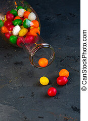 side view of colorful candies in a glass bottle on black background