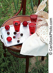 side view of compote with cherries in glasses on a silver tray