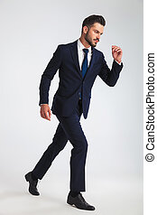 side view of confident businessman in navy suit stepping