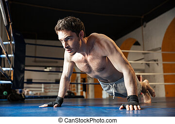 Side view of cool boxer doing push ups