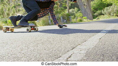Side view of cool young caucasian man doing skateboard trick on downhill at countryside road 4k