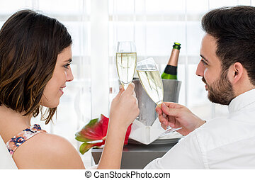 Side view of couple celebrating with sparkling wine.