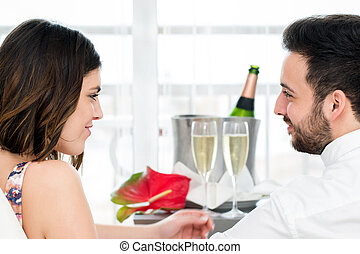 Side view of couple with sparkling wine in background.