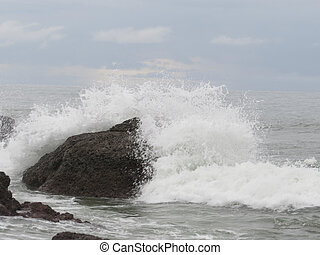 side view of crashing wave against rock - side vview of ...