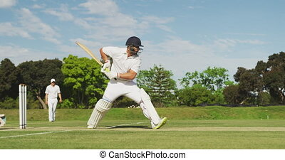 Side view of cricket player shooting in the ball - Side view...