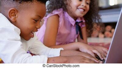 Side view of cute black siblings using laptop in living room at comfortable home 4k